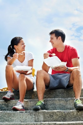 A smiling couple in fitness clothing sitting on a set of steps e